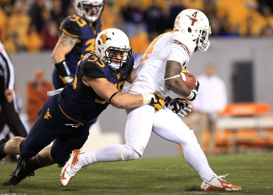 Texas 47, West Virginia 40 (OT)Record: 7-2  West Virginia's Nick Kwiatkowski (35) tackles Texas' Daje Johnson (4) during the third quarter of their NCAA college football game in Morgantown, W.Va., on Saturday, Nov.9, 2013. Texas won 47-40 in overtime. (AP Photo/Christopher Jackson) Photo: Chris Jackson, Associated Press