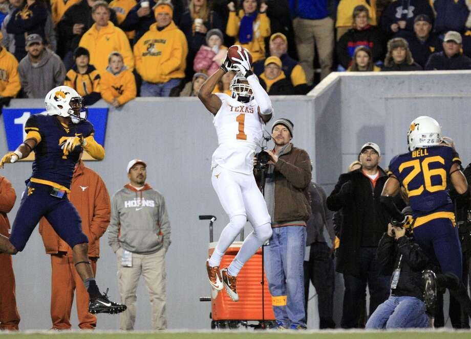 Texas' Mike Davis (1) makes a catch between West Virginia's Daryl Worley (7) and Travis Bell (26) during the fourth quarter of their NCAA college football game in Morgantown, W.Va., on Saturday, Nov.9, 2013. Texas won 47-40 in overtime. (AP Photo/Christopher Jackson) Photo: Chris Jackson, Associated Press