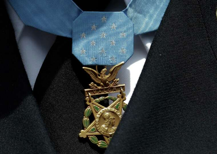 The Medal of Honor is worn by Army Staff Sgt. Ty Michael Carter, after throwing out the ceremonial f