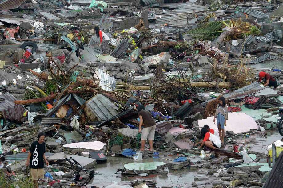 Residents try to salvage belongings in Tacloban city, Leyte province, central Philippines on Sunday, Nov. 10, 2013. The city remains littered with debris from damaged homes as many complain of shortages of food and water and no electricity since Typhoon Haiyan slammed into their province. Haiyan, one of the most powerful storms on record, slammed into six central Philippine islands on Friday, leaving a wide swath of destruction and scores of people dead. Photo: Bullit Marquez, AP / AP
