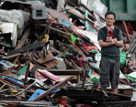 A resident looks at houses damaged by typhoon Haiyan, in Tacloban city, Leyte province central Philippines on Sunday, Nov. 10, 2013. Haiyan, one of the most powerful typhoons ever recorded slammed into central Philippine provinces Friday leaving a wide swath of destruction and scores of people dead. Photo: Aaron Favila, AP / AP