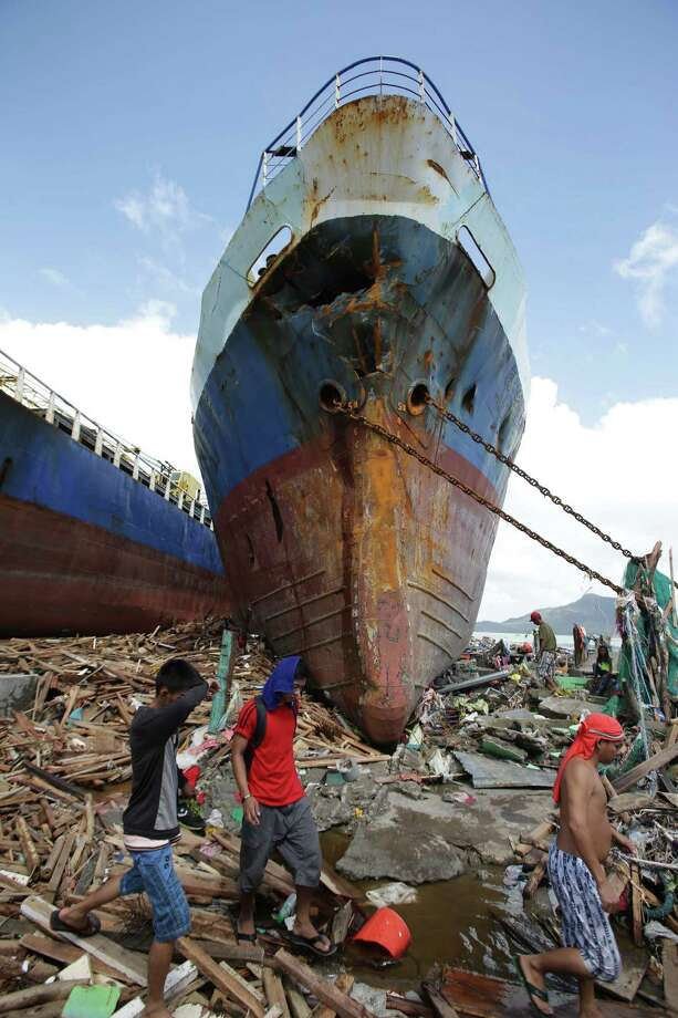 Survivors walk by a large ship after it was washed ashore by strong waves caused by powerful Typhoon Haiyan in Tacloban city, Leyte province, central Philippines on Sunday, Nov. 10, 2013. The city remains littered with debris from damaged homes as many complain of shortages of food and water and no electricity since Typhoon Haiyan slammed into their province. Haiyan, one of the most powerful storms on record, slammed into six central Philippine islands on Friday, leaving a wide swath of destruction and scores of people dead. Photo: Aaron Favila, AP / AP