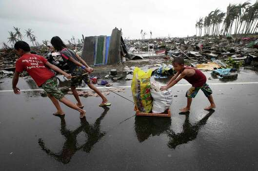 Residents carry relief goods past damaged homes in Tacloban city, Leyte province, central Philippines on Sunday, Nov. 10, 2013. The city remains littered with debris from damaged homes as many complain of shortages of food and water and no electricity since Typhoon Haiyan slammed into their province. Haiyan, one of the most powerful storms on record, slammed into six central Philippine islands on Friday, leaving a wide swath of destruction and scores of people dead. Photo: Bullit Marquez, AP / AP
