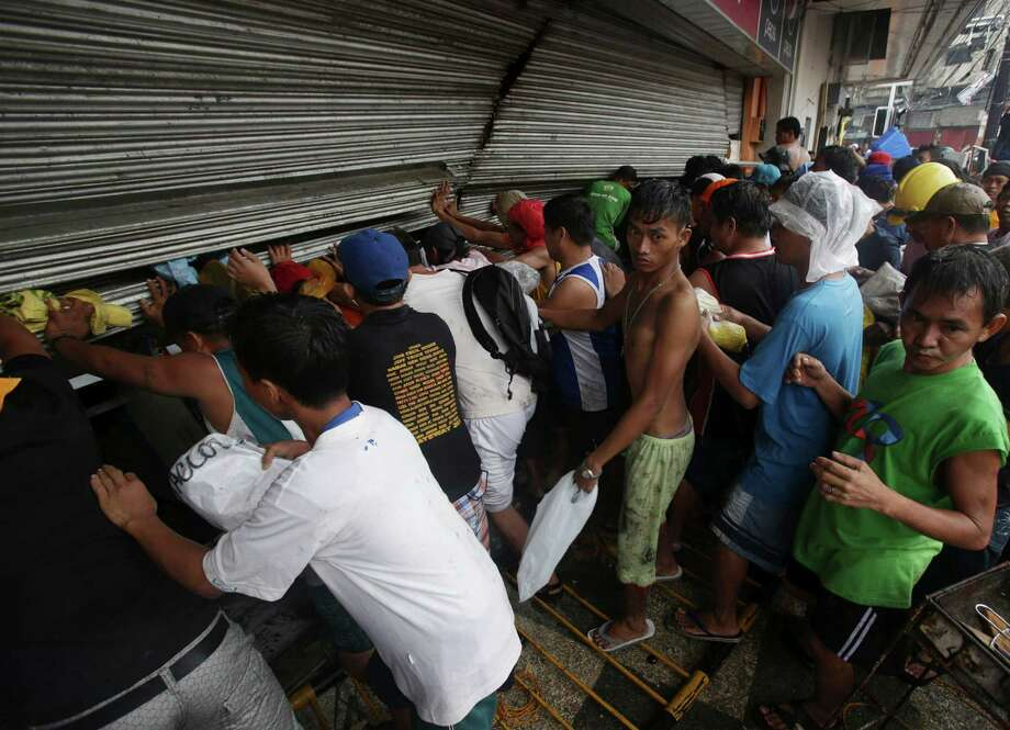Residents push a shutter to open a small grocery to get food in Tacloban city, Leyte province central Philippines on Sunday, Nov. 10, 2013. The city remains littered with debris from damaged homes as many complain of shortage of food, water and no electricity since the Typhoon Haiyan slammed into their province. Photo: Aaron Favila, AP / AP
