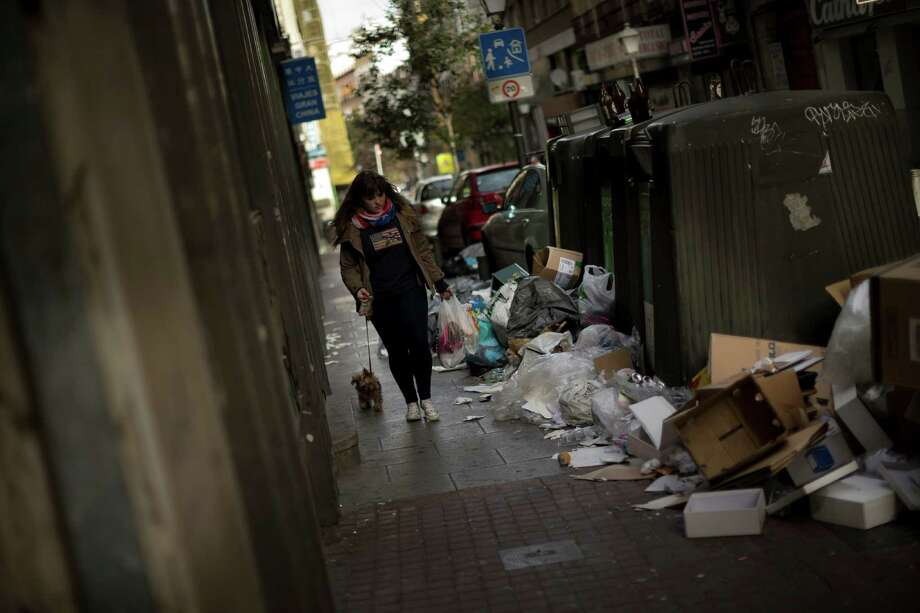 A girl walks her dog by containers already piled up with trash bags during the sixth day of a garbage collectors strike, in Madrid, Sunday, Nov. 10, 2013. Street cleaners and garbage collectors who work in the city's public parks walked off the job in a strike called by trade unions to contest the planned layoff of more than 1,000 workers. Madrid's municipal cleaning companies, which have service supply contracts with the city authorities, employ some 6,000 staff. Photo: Daniel Ochoa De Olza, AP / AP