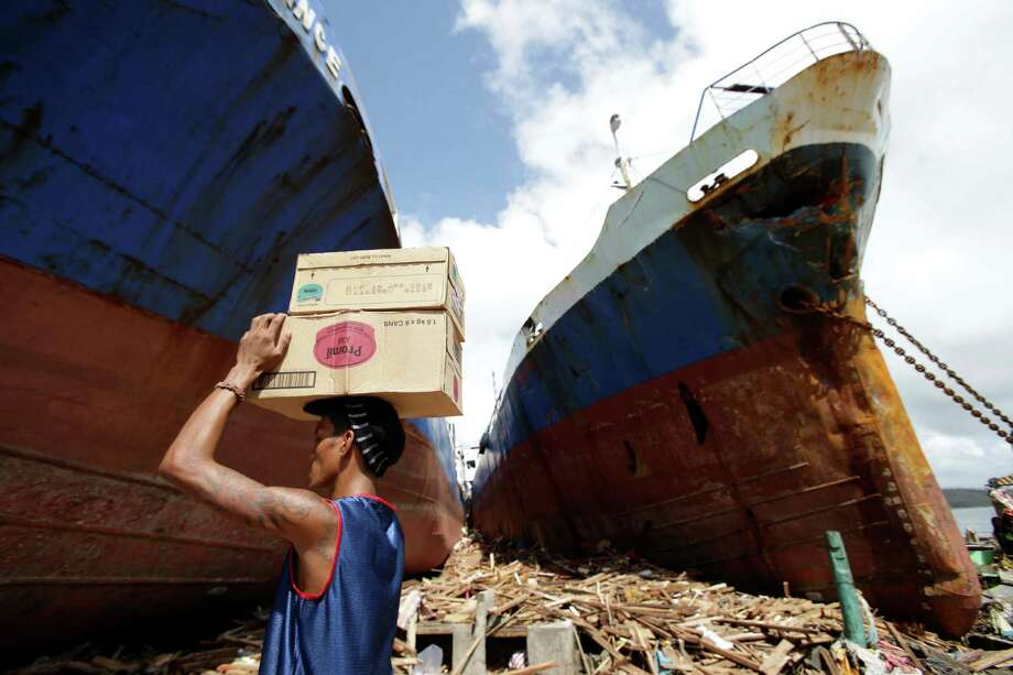A resident carries boxes of milk as he passes by ships washed ashore by strong waves in Tacloban city, Leyte province central Philippines on Sunday, Nov. 10, 2013. The city remains littered with debris from damaged homes as many complain of shortage of food, water and no electricity since the Typhoon Haiyan slammed into their province. Haiyan, one of the most powerful typhoons ever recorded, slammed into central Philippine provinces Friday leaving a wide swath of destruction and scores of people dead. Photo: Aaron Favila, AP / AP