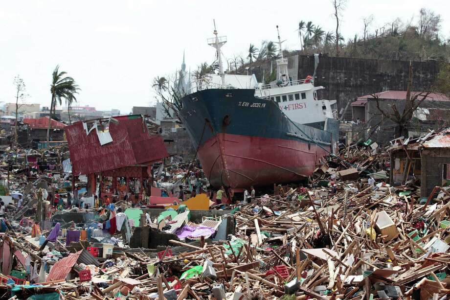 Survivors walk past a ship that lies on top of damaged homes after it was washed ashore in Tacloban city, Leyte province central Philippines on Sunday, Nov. 10, 2013. The city remains littered with debris from damaged homes as many complain of shortage of food, water and no electricity since the Typhoon Haiyan slammed into their province. Haiyan, one of the most powerful typhoons ever recorded, slammed into central Philippine provinces Friday leaving a wide swath of destruction and scores of people dead. Photo: Aaron Favila, AP / AP2013