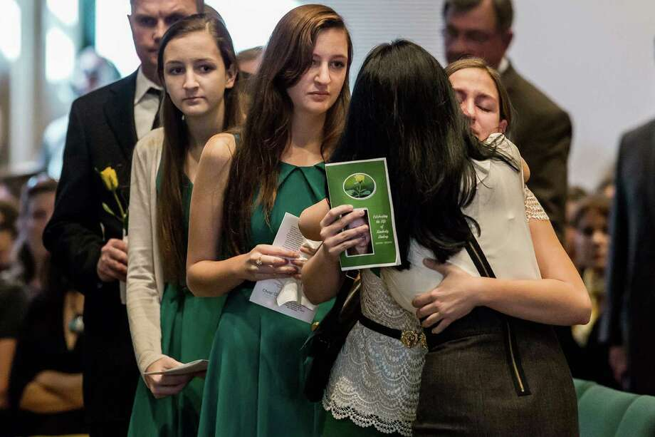 Left to right: Savannah, Sofia and Sarah Lambert are greeted with a hug as hundreds of friends and family filled Smith Chapel at Christ Fellowship's South Campus in Palm Beach Gardens, Fla. for  Kimberly Lindsey's memorial service on Wednesday, Nov. 6, 2013. Lindsey, 49, was reported missing Oct. 28 and her body found Oct. 30 in a cane field south of Clewiston. (AP Photo/Palm Beach Post, Thomas Cordy)  Photo: Thomas Cordy, AP / AP2013