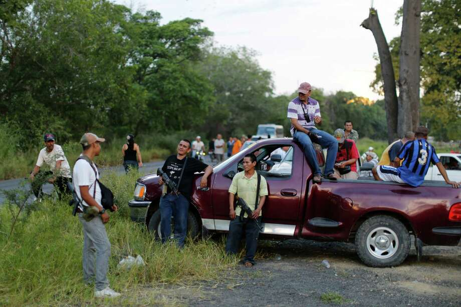 In this Nov. 5 photo, villagers who are members of the local self-defense group gather to block a road in response to soldiers allegedly confiscating a handful of their weapons in Las Colonias, Mexico. The group says that soldiers confiscated a few of their weapons and that their leaders were negotiating with the army to get them back. The self-defense groups started small with just a few dozen civilians from a couple of communities_lime pickers, ranchers and business owners who began patrolling the streets, setting up roadblocks and ambushing the Knights Templar as the drug men roamed with their heavy artillery and SUVs. Photo: Dario Lopez-Mills, AP / AP2013