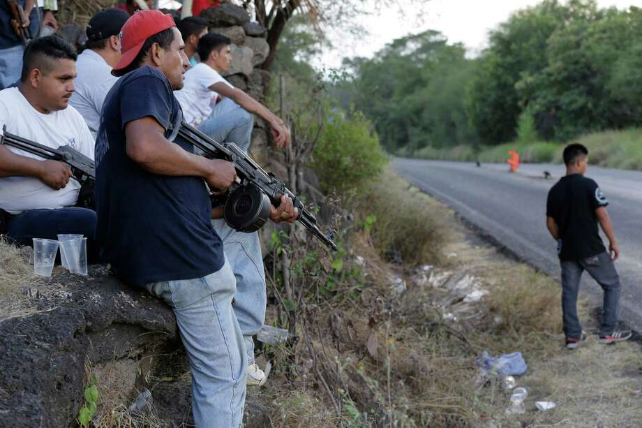 In this Nov. 5 photo, villagers belonging to a self-defense group stand at a checkpoint in the town of Las Colonias, in the state of Michoacan, Mexico. Self-defense groups now claim several thousand members, competing with the Kights Templar cartel in raw numbers if not firepower. Photo: Dario Lopez-Mills, AP / AP2013