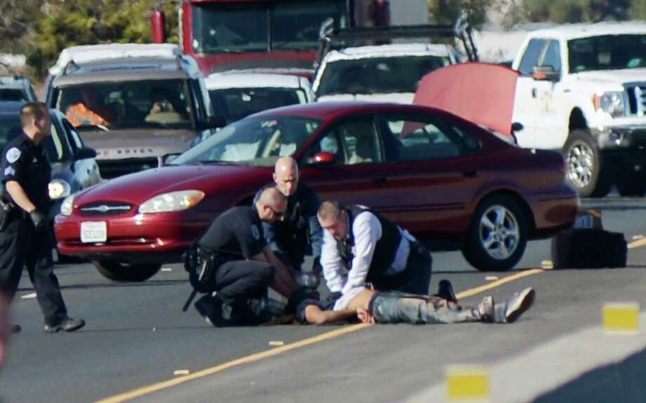 Fairfield police treat a man who was shot by police Tuesday Nov. 5, 2013, on Highway 12 in Fairfield, Calif. The man is suspected of stabbing a woman in an apartment complex on the 200 block of Pennsylvania Avenue. Photo: Robinson Kuntz, AP / - The Daily Republic