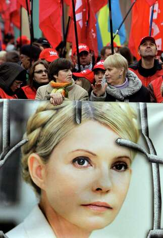 Activist of the Ukrainian Opposition Party stand by a poster with the image of former Ukrainian Prime Minister Yulia Tymoshenko, during a rally in front of parliament building in Kiev, Ukraine, Thursday, Nov. 7, 2013. The trial of the former prime minister for tax evasion was adjourned Wednesday until after the Eastern Partnership Summit, at which Kiev plans to sign partnership deals with the EU. Photo: Sergei Chuzavkov, AP / AP2013