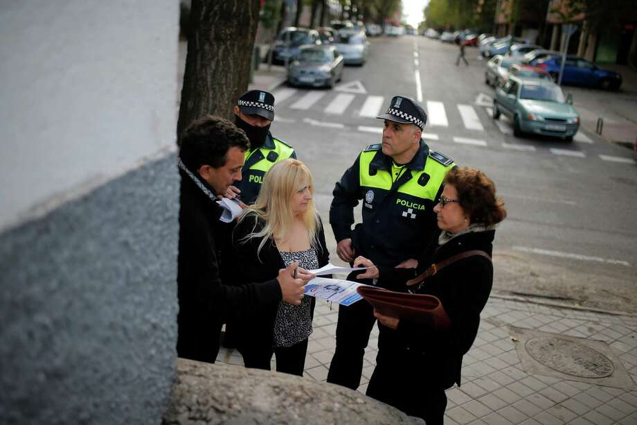 Dori Galletero, who is 47 and unemployed, third from left, hands a written agreement to leave the apartment in two months to a Kutxa bank representative, right, following the postponement of her eviction in Madrid, Spain, Tuesday, Nov. 5, 2013. Galletero lives with her 25-year-old daughter Noelia, who has a part-time job and her 14-year-old son. Galletero purchased a euro 240,000 (US$323,000) apartment by taking a mortgage with Kutxa bank in 2006, but ceased making payments after losing her job in 2010. Her income consists of euro 680 (US$ 916) from Noelia's part-time job and state benefits of euro 426 (US$ 646). The eviction was postponed for two months with the help of the Victims' Mortgage Platform (PAH). Photo: Andres Kudacki, AP / AP