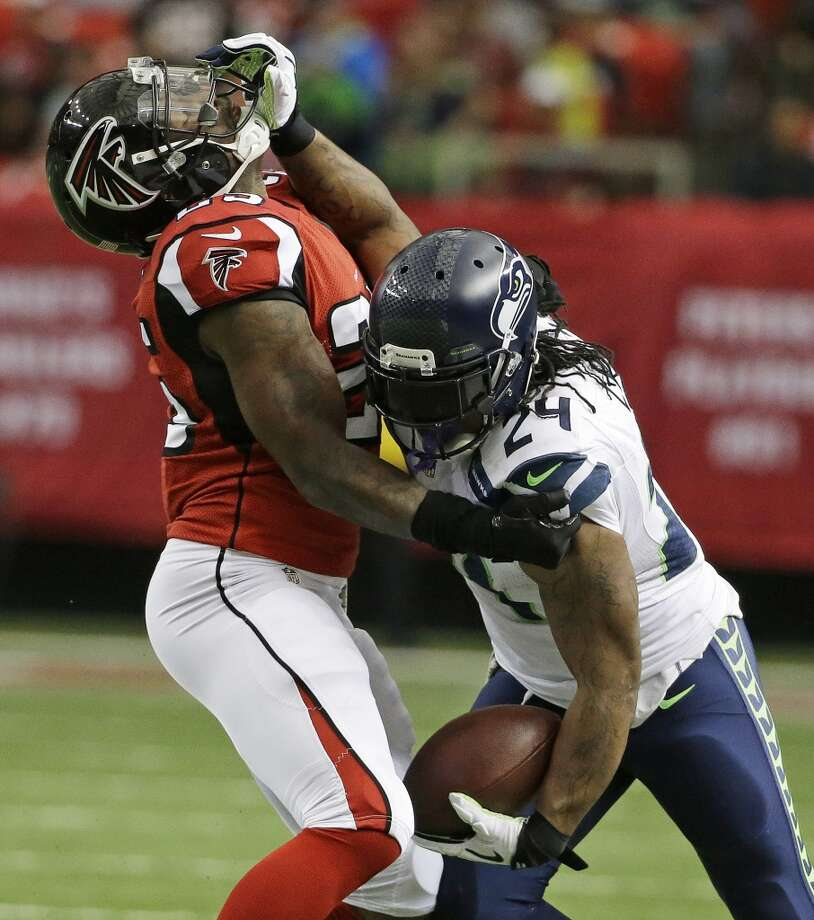 Seattle Seahawks running back Marshawn Lynch (24) strait arms Atlanta Falcons strong safety William Moore (25) during the first half of an NFL football game, Sunday, Nov. 10, 2013, in Atlanta. (AP Photo/David Goldman) Photo: AP