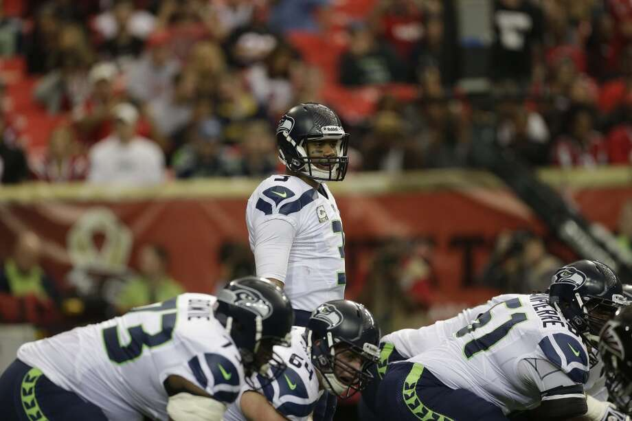 Seattle Seahawks quarterback Russell Wilson (3) works against the Atlanta Falconsduring the first half of an NFL football game, Sunday, Nov. 10, 2013, in Atlanta. (AP Photo/John Bazemore) Photo: AP