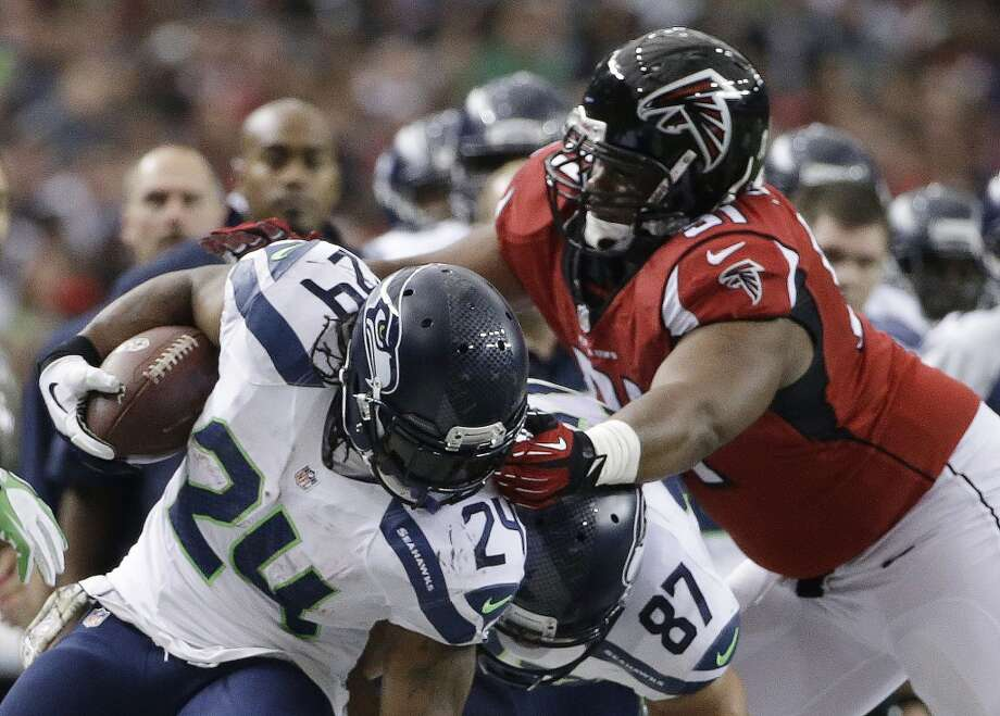 Seattle Seahawks running back Marshawn Lynch (24) is stopped by Atlanta Falcons defensive tackle Corey Peters (91) during the first half of an NFL football game, Sunday, Nov. 10, 2013, in Atlanta. (AP Photo/David Goldman) Photo: AP