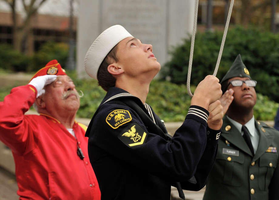 Navy Sea Cadet Jonathan Welborn, center, brings the American flag to half-staff during the playing of Taps as Pasquale Batinelli, left, and Westhill JROTC member Kyle Turner salute during the Veterans Day ceremony in Veterans Park in downtown Stamford, Conn., on Sunday, Nov. 10, 2013. Photo: Jason Rearick / Stamford Advocate