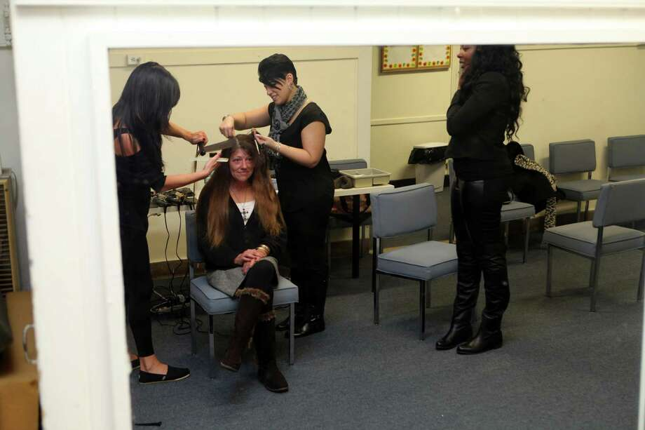 Darcy Apicella, left,  Jessica Palmeri, and Candice Jones, right, all of Milano Day Spa in Bloomfield,  cut and style the hair of Dawn Brown, of Bridgeport, at the 2013 Community Outreach Beauty Event sponsored by Empowering Through Beauty, Inc. on Sunday, Nov. 10, 2013 at the Norma F. Pfriem Urban Outreach Initiatives in Bridgeport. Photo: BK Angeletti, B.K. Angeletti / Connecticut Post freelance B.K. Angeletti