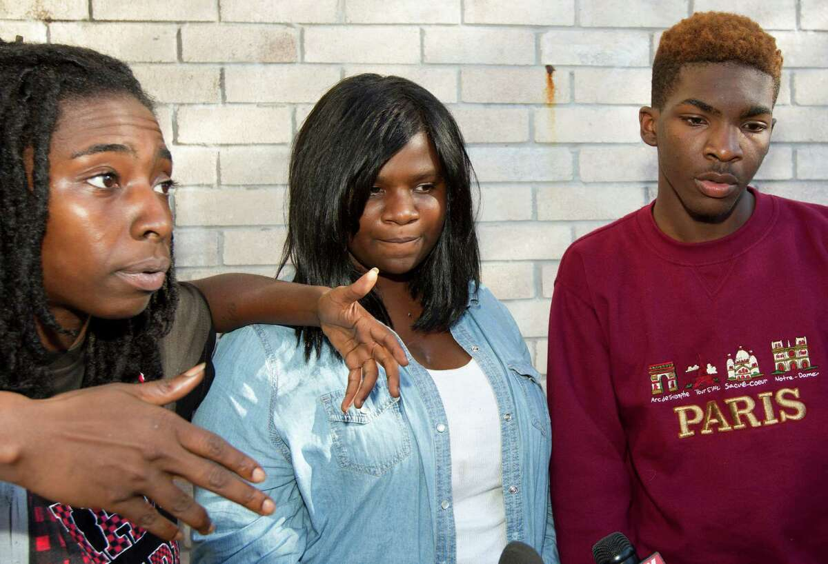"""Partygoers B.T. Tucker, left, Mariah Boulden, 18, center, and Lank, who wished to only be referred by his first name, talk to the media Sunday, Nov. 10, 2013 outside Mariah's home where two people were killed and at least 20 others injured late Saturday when gunfire erupted during her birthday party in the Cypress area in Houston. Harris County Sheriff Adrian Garcia said the gathering Saturday night that drew more than 100 people, most of them 17- to 19-year-olds, became a """"birthday party gone wild."""" (AP Photo/Houston Chronicle, J. Patric Schneider)"""