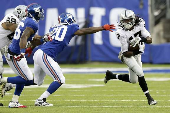 Oakland Raiders wide receiver Denarius Moore (17) runs with the ball as New York Giants cornerback Prince Amukamara (20) reaches out during the second half of an NFL football game, Sunday, Nov. 10, 2013, in East Rutherford, N.J. The Giants won 24-20. (AP Photo/Kathy Willens)