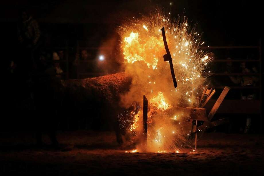 "In this photo taken on Saturday, Nov. 9, 2013, revellers watch as fire bull crashes one of the five bonfires set around the area during the 'Toro de Jubilo' Fire Bull Festival in Medinaceli, Spain. Fire bull Festival ""Toro de Jubilo"" that takes place in the main square of Medinaceli is an ancient tradition from the bronze age. During the event a bull is tied to a pylon and flammable balls attached to the bull's horns are set on fire before the animal released. Revelers dodge the bull when it comes close until the flammable material is consumed. The bull is covered with a thick layer of mud on the back and face to protect it from burns. Photo: Andres Kudacki, AP / AP"