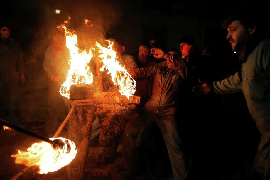 "In this photo taken on Saturday, Nov. 9, 2013, revelers set the horns of the bull on fire, centre down, during the 'Toro de Jubilo' Fire Bull Festival in Medinaceli, Spain. Fire bull Festival ""Toro de Jubilo"" that takes place in the main square of Medinaceli is an ancient tradition from the bronze age. During the event a bull is tied to a pylon and flammable balls attached to the bull's horns are set on fire before the animal released. Revelers dodge the bull when it comes close until the flammable material is consumed. The bull is covered with a thick layer of mud on the back and face to protect it from burns. Photo: Andres Kudacki, AP / AP"