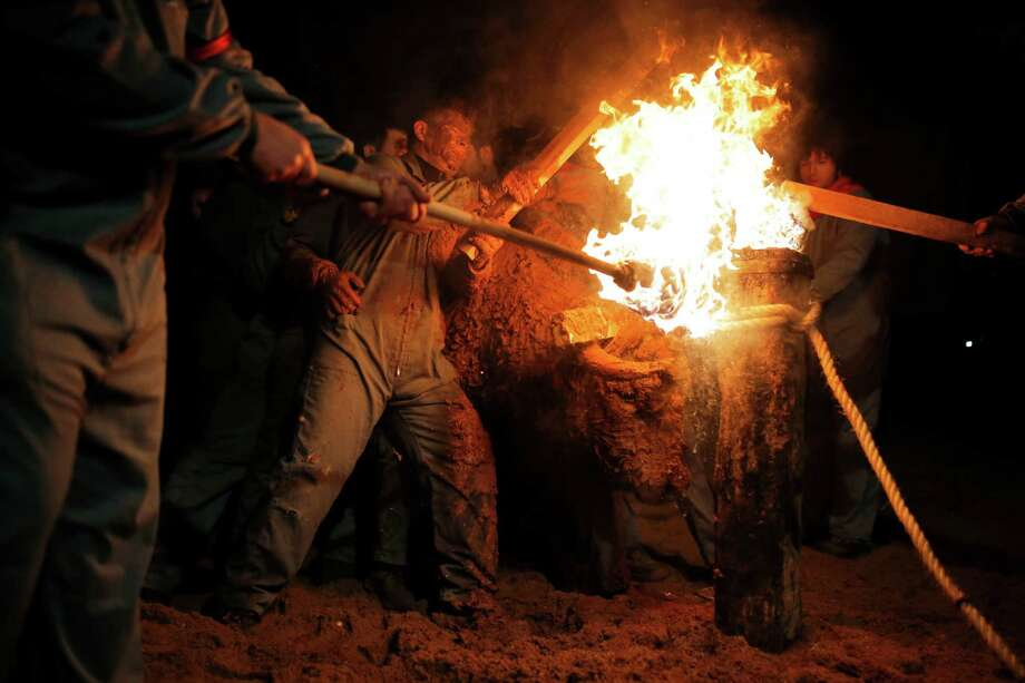 "In this photo taken on Saturday, Nov. 9, 2013, revelers set on fire the horns of the bull, right, during the 'Toro de Jubilo' Fire Bull Festival in Medinaceli, Spain. Fire bull Festival ""Toro de Jubilo"" that takes place in the main square of Medinaceli is an ancient tradition from the bronze age. During the event a bull is tied to a pylon and flammable balls attached to the bull's horns are set on fire before the animal released. Revelers dodge the bull when it comes close until the flammable material is consumed. The bull is covered with a thick layer of mud on the back and face to protect it from burns. Photo: Andres Kudacki, AP / AP"