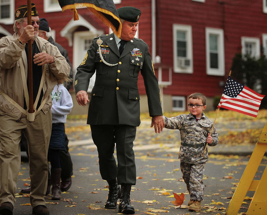 Wyatt Gaffney, 3, marches with his grandfather, Vietnam veteran Tom Johnson, of Milford, in the Veteran's Day Parade in Milford, Conn. on Sunday, November 10, 2013. Photo: Brian A. Pounds / Connecticut Post