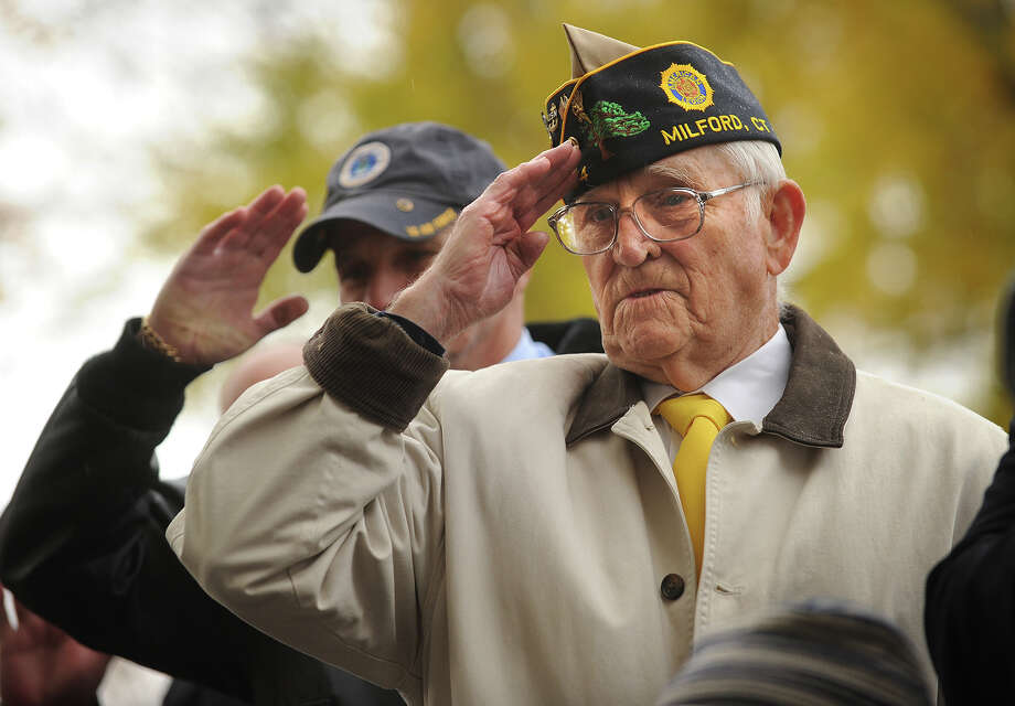 Parade grand marshall and Korean War vet Wayne Carson, right, salutes from the reviewing stand the Veteran's Day Parade in Milford, Conn. on Sunday, November 10, 2013. Photo: Brian A. Pounds / Connecticut Post