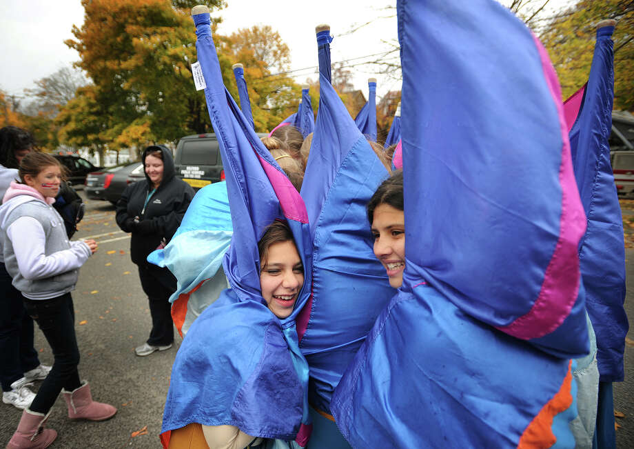 Members of the Jonathan Law High School Color Guard, Brooke Kolliopoulos, left, and Lilah Khan, wrap themselves in their flags to keep warm before the start of the Veteran's Day Parade in Milford, Conn. on Sunday, November 10, 2013. Photo: Brian A. Pounds / Connecticut Post
