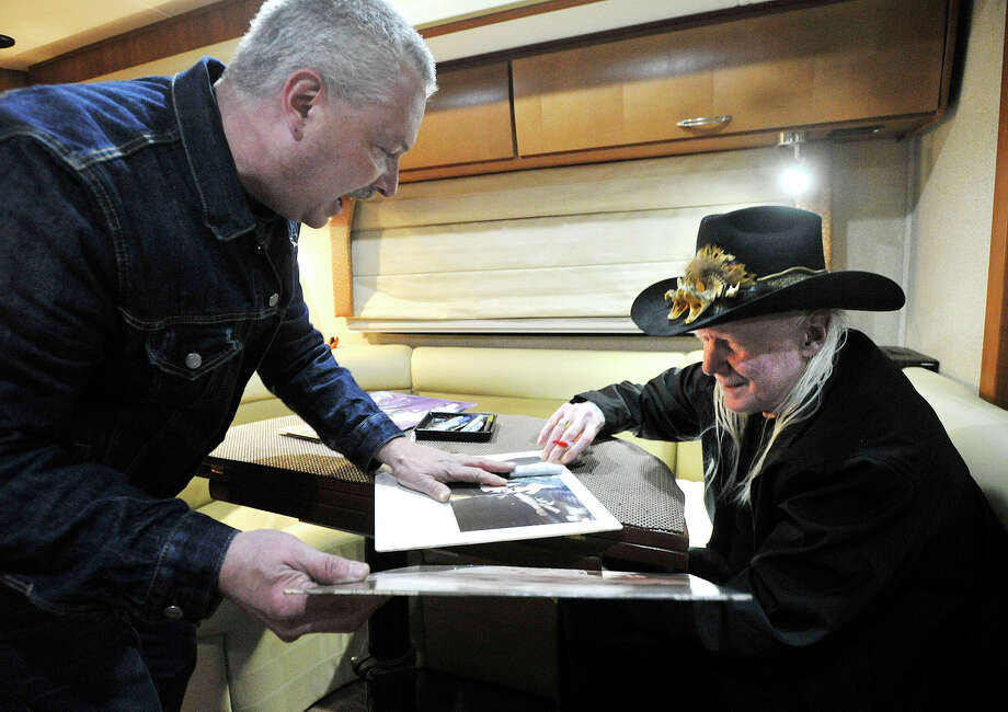 Blues guitarist Johnny Winter, right, signs autographs for David Lynch in his tour bus outside Johnny's, a record store in Darien, Conn., before performing in Fairfield later that night on Sunday, Nov. 10, 2013. Photo: Jason Rearick / Stamford Advocate