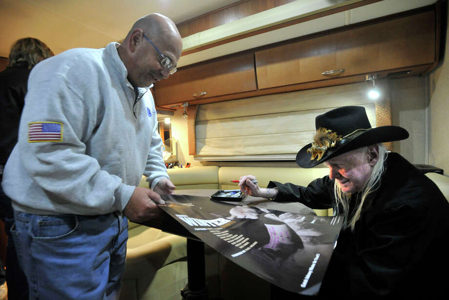 Mike Lascalo, left, gets a poster autographed by blues guitarist Johnny Winter in his tour bus outside Johnny's, a record store in Darien, Conn., before performing in Fairfield later that night on Sunday, Nov. 10, 2013. Photo: Jason Rearick / Stamford Advocate
