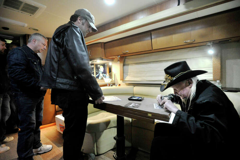 Blues guitarist Johnny Winter, right, signs autographs for Lou Macri in his tour bus outside Johnny's, a record store in Darien, Conn., before performing in Fairfield later that night on Sunday, Nov. 10, 2013. Photo: Jason Rearick / Stamford Advocate