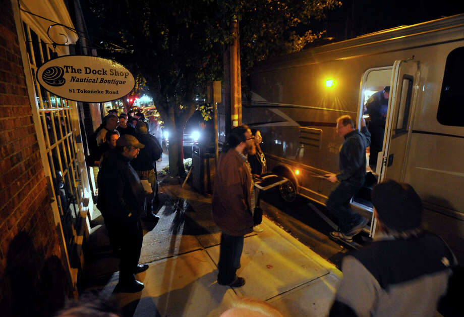 Fans of blues guitarist Johnny Winter wait in a line outside his tour bus before being called to meet the musician outside Johnny's, a record store in Darien, Conn., before Winter performed in Fairfield later that night on Sunday, Nov. 10, 2013. Photo: Jason Rearick / Stamford Advocate