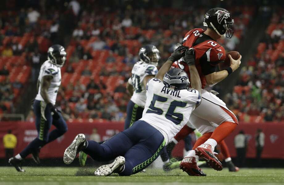 Seattle Seahawks linebacker Heath Farwell (55) makes a horse-collar tackle against Atlanta Falcons quarterback Matt Ryan (2) during the second half of an NFL football game, Sunday, Nov. 10, 2013, in Atlanta. Farwell  was charged with a penalty. (AP Photo/David Goldman) Photo: AP