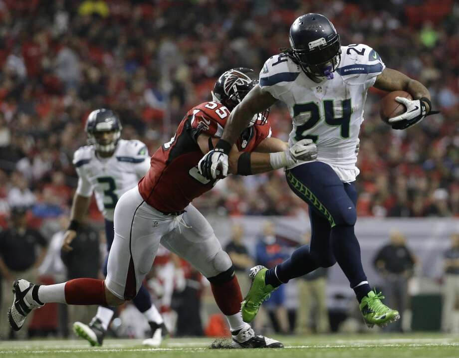 Seattle Seahawks running back Marshawn Lynch (24) moves the ball as Atlanta Falcons outside linebacker Paul Worrilow (55) holds on during the second half of an NFL football game, Sunday, Nov. 10, 2013, in Atlanta. (AP Photo/David Goldman) Photo: AP