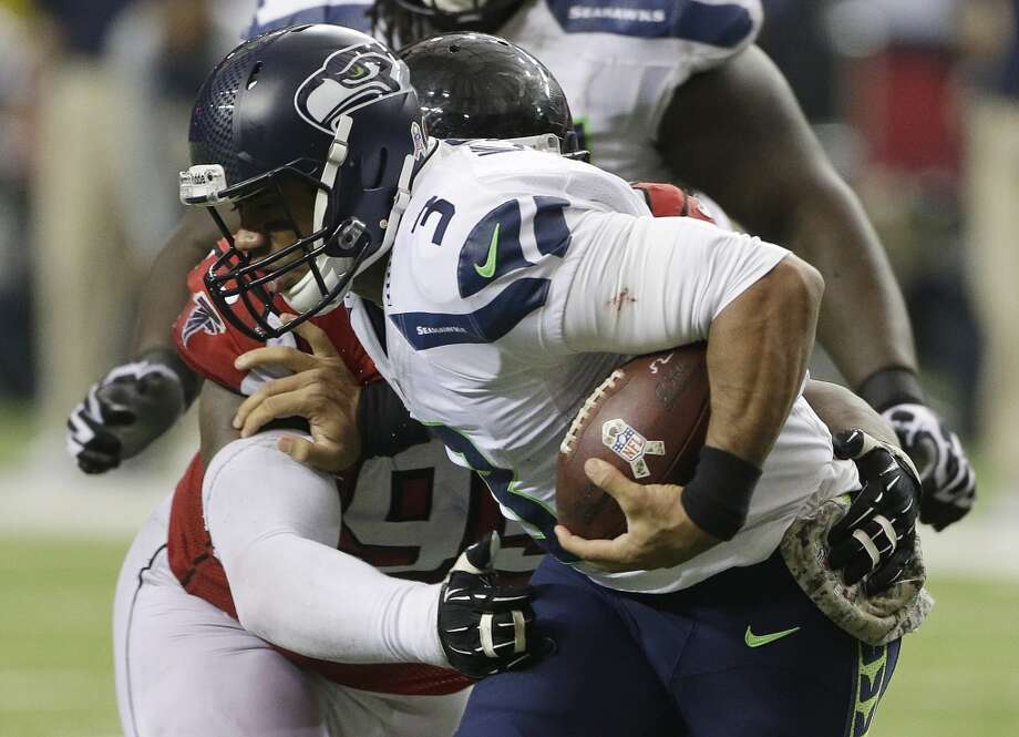 Atlanta Falcons defensive tackle Jonathan Babineaux (95) hits Seattle Seahawks quarterback Russell Wilson (3) during the second half of an NFL football game, Sunday, Nov. 10, 2013, in Atlanta. (AP Photo/John Bazemore) Photo: AP
