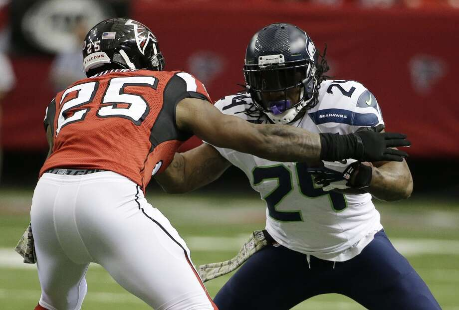Seattle Seahawks running back Marshawn Lynch (24) works against Atlanta Falcons strong safety William Moore (25) during the first half of an NFL football game, Sunday, Nov. 10, 2013, in Atlanta. (AP Photo/David Goldman) Photo: AP