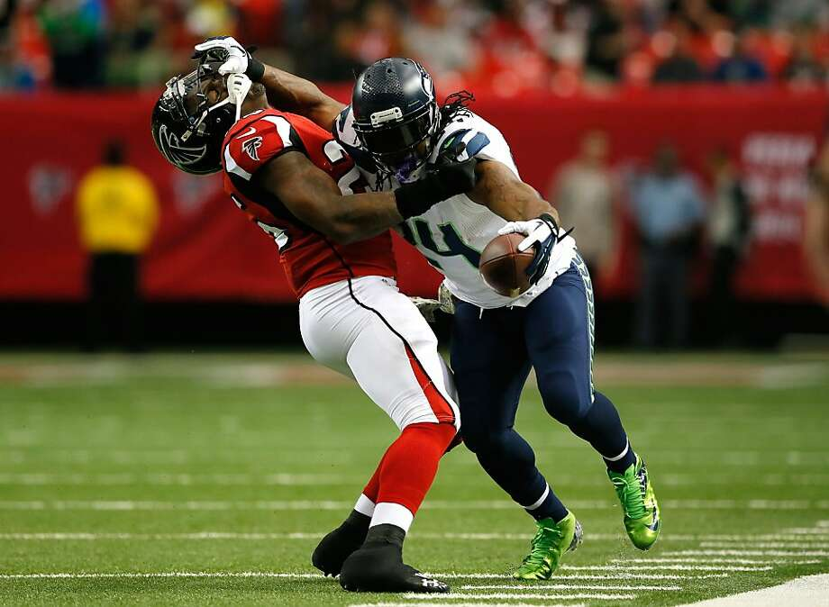 Seattle's Marshawn Lynch, who rushed for 145 yards, stiff-arms Atlanta's William Moore. Photo: Kevin C. Cox, Getty Images