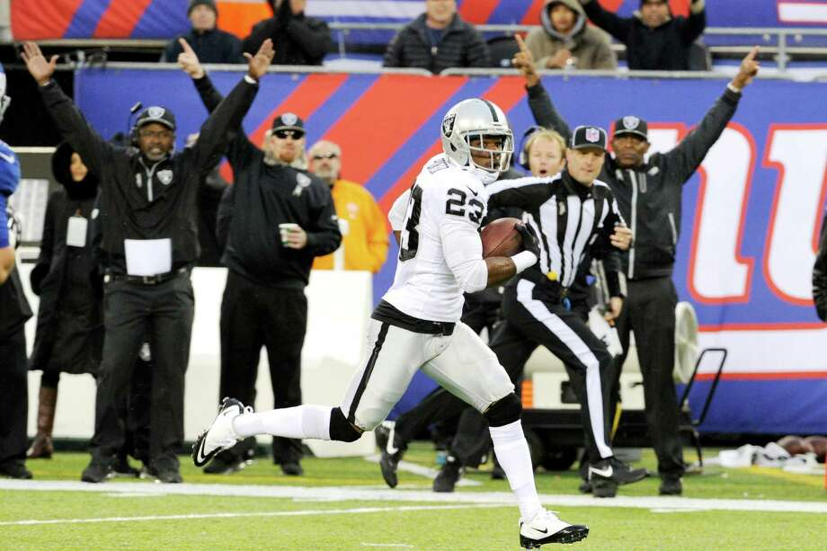 Oakland Raiders cornerback Tracy Porter (23) runs in a touchdown after intercepting a pass from New York Giants quarterback Eli Manning during the first half of an NFL football game on Sunday, Nov. 10, 2013, in East Rutherford, N.J. (AP Photo/Bill Kostroun) ORG XMIT: ERU118 Photo: Bill Kostroun / FR51951 AP