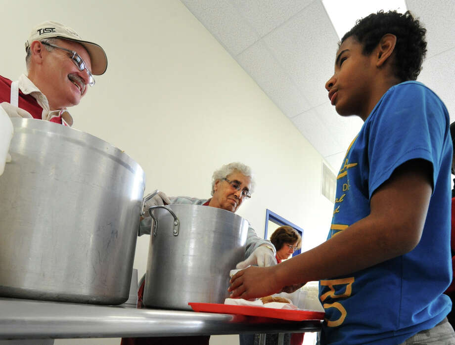 From left, volunteers Matt Babcock and Sister Pat Newell serves hot soup to Felton Perez, 13, of Albany at the soup kithcen at the Sister Maureen Joyce Center Monday, Oct. 8, 2012 in Albany, N.Y. (Lori Van Buren / Times Union) Photo: Lori Van Buren / 00019558A