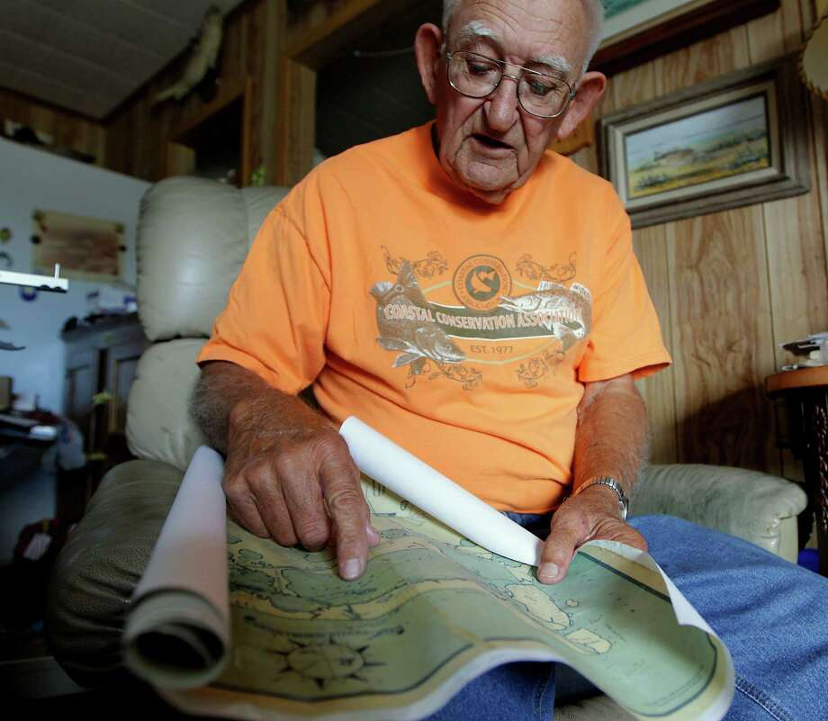 Lloyd Pepper, a veteran Galveston Bay fishing guide and longtime custom fishing rod builder, holds an old fishing chart Thursday. He built a solid reputation in the tackle industry. Photo: James Nielsen, Staff / © 2013  Houston Chronicle