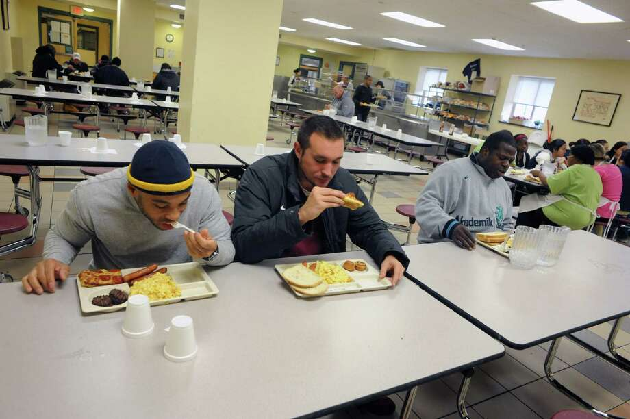 Jerry Mitchell, left, and James Kennedy, Center, both participants in the mission's New Life Program have lunch at the Capital City Rescue Mission on Saturday Nov. 9, 2013 in Albany, N.Y. (Michael P. Farrell/Times Union) Photo: Michael P. Farrell / 00024573A