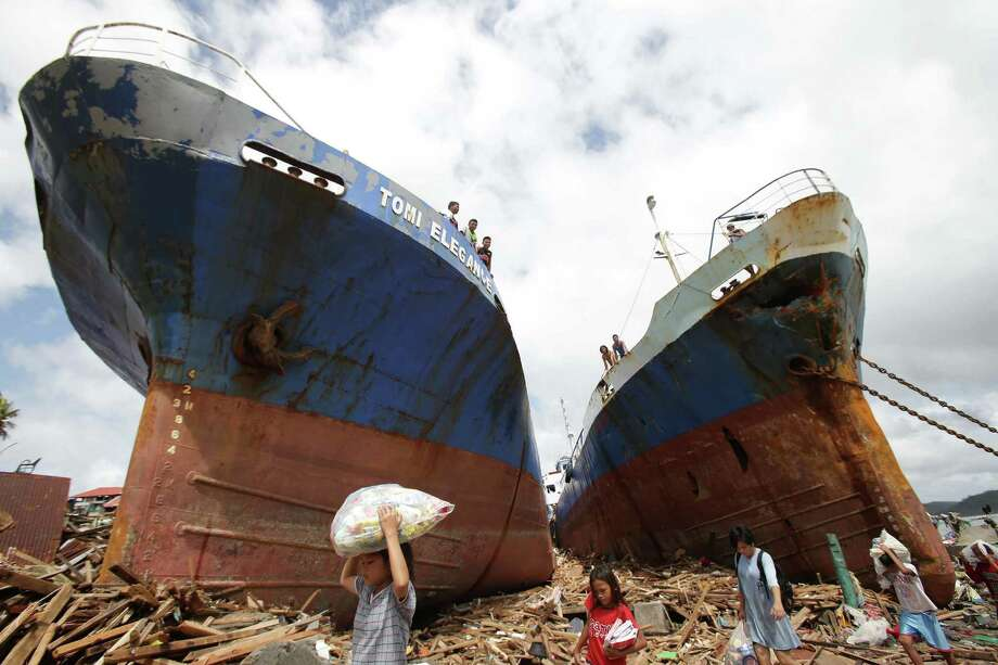 Survivors pass by two large boats after they were washed ashore by strong waves caused by Typhoon Haiyan in Tacloban city, Leyte province central Philippines on Sunday, Nov. 10, 2013. Typhoon Haiyan, one of the strongest storms on record, slammed into six central Philippine islands on Friday leaving a wide swath of destruction and hundreds of people dead.    (AP Photo/Aaron Favila) ORG XMIT: XAF102 Photo: Aaron Favila / AP