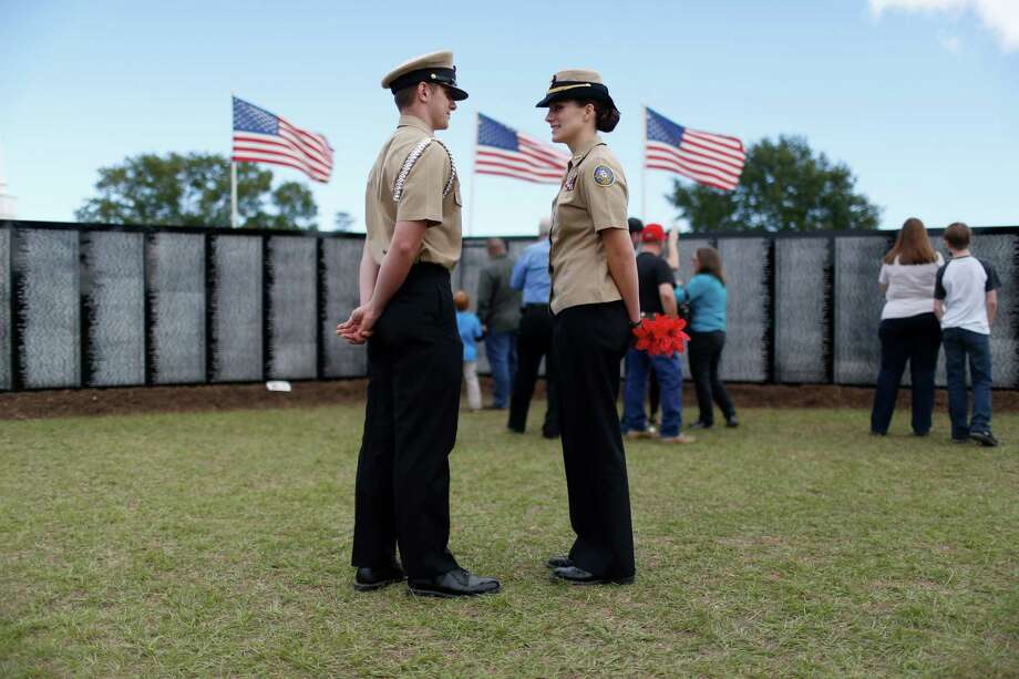 Magnolia High School Navy JROTC students Dorian Lockhart, 17, left, and Elizabeth Brittain, 18, chat as visitors pay their respects at a miniature, traveling display of the Vietnam War Memorial  Nov. 10, 2013 in Magnolia, TX. Photo: Eric Kayne, For The Chronicle / Eric Kayne