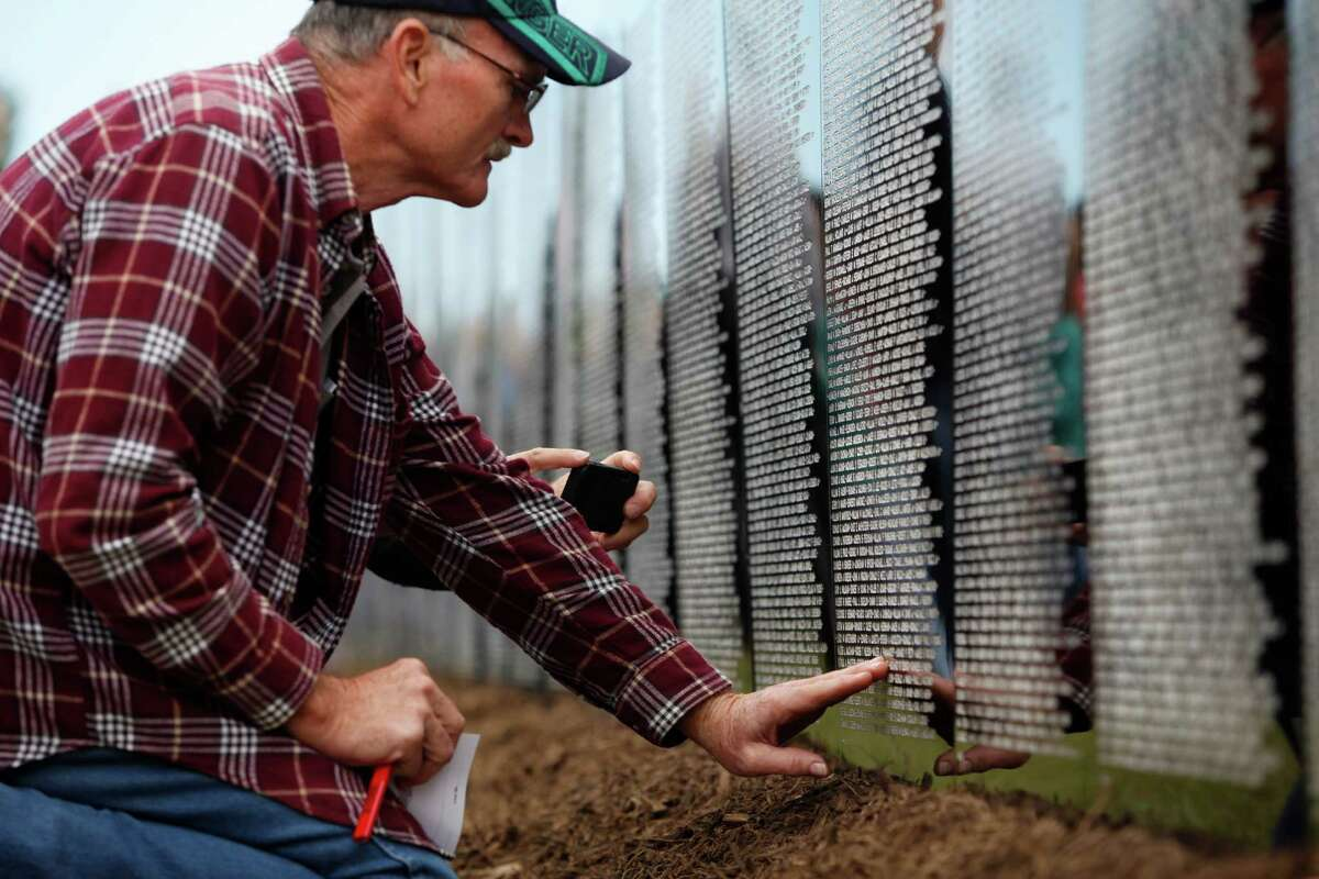 John David Floyd touches a name on a Vietnam War Memorial replica after making a pencil impression as visitors pay their respects at a miniature, traveling display of the Vietnam War Memorial Nov. 10, 2013 in Magnolia, TX.