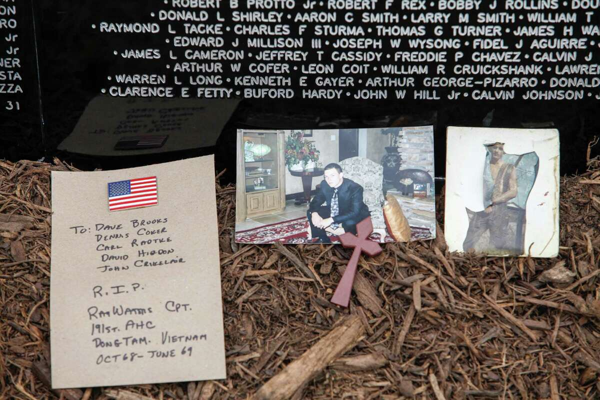 Mementos are laid at the base of the wall as visitors pay their respects at a miniature, traveling display of the Vietnam War Memorial Nov. 10, 2013 in Magnolia, TX.