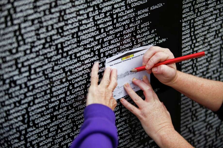 Diana Baxter, left, and Trudy Baxter make an impression of a name on a Vietnam War Memorial replica as visitors pay their respects at a miniature, traveling display of the Vietnam War Memorial  Nov. 10, 2013 in Magnolia, TX. The person on the wall was a classmate's of Diana's in Fostoria, Ohio. Photo: Eric Kayne, For The Chronicle / Eric Kayne