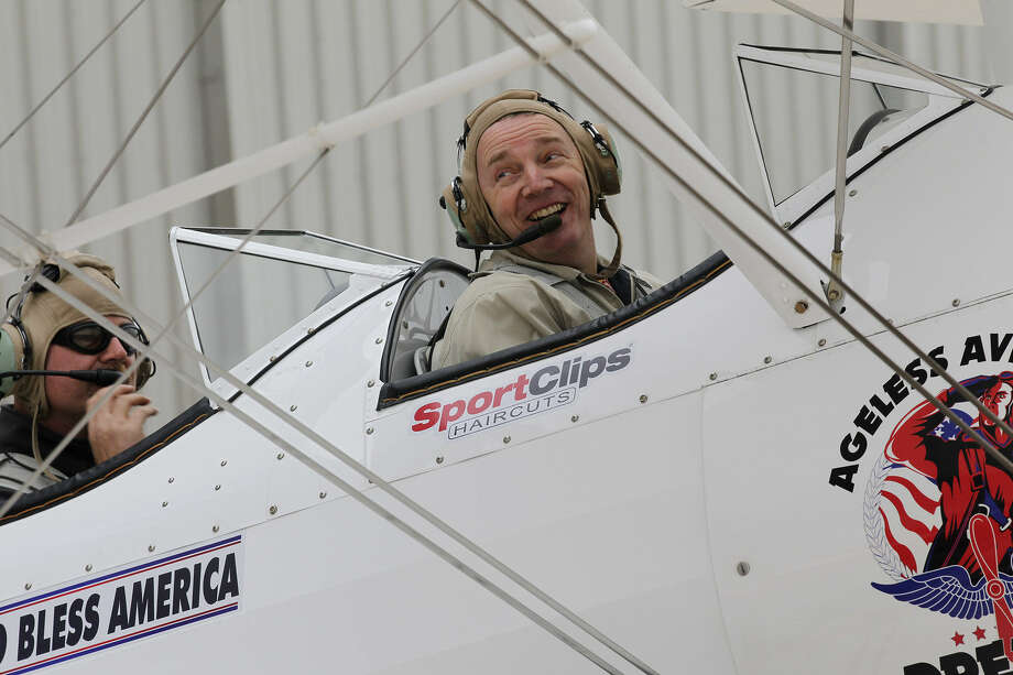 Retired Marine Gunnery Sgt. Dave Shoemaker (right), 56, smiles as he sits in the cockpit of a 1943 Boeing Stearman biplane at San Antonio International Airport. Darryl Fisher of nonprofit Ageless Aviation Dreams Foundation piloted the plane. Photo: Photos By Jerry Lara / San Antonio Express-News