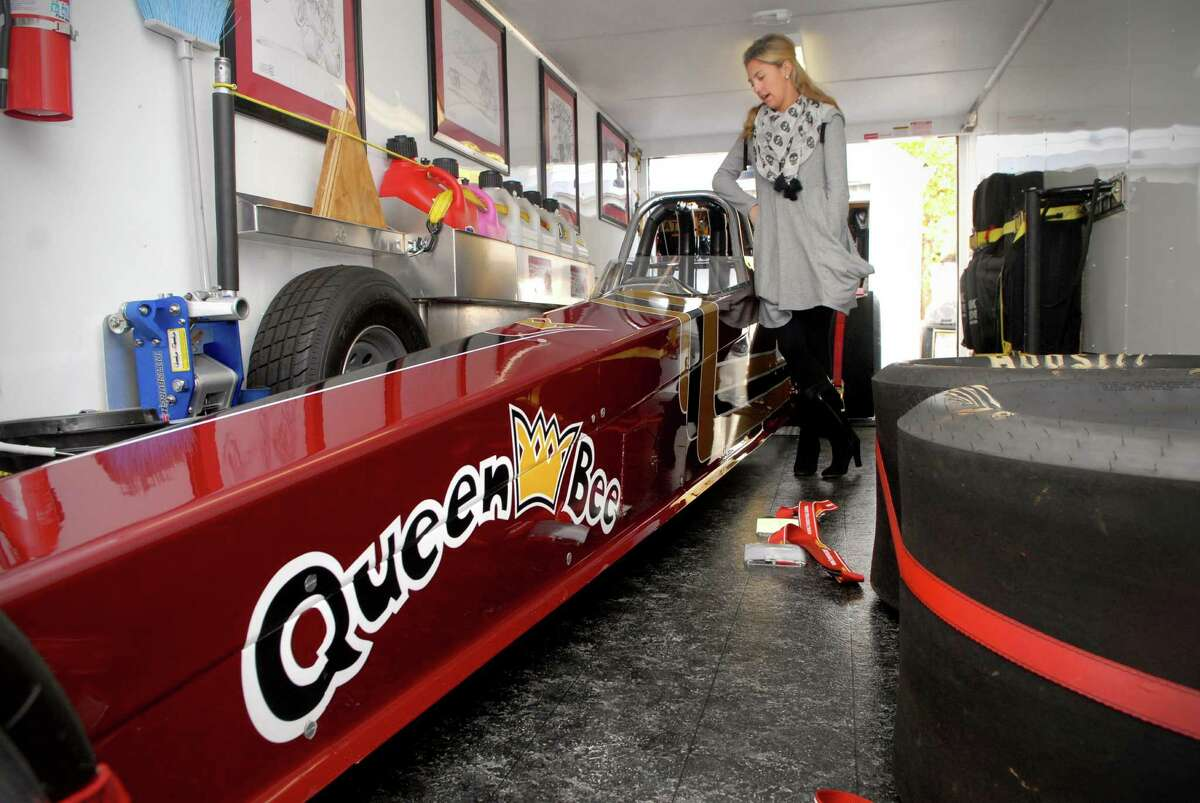 Sarah Edwards poses in her trailer on Monday October 28, 2013 in Stamford, Conn. with the car she drag races.